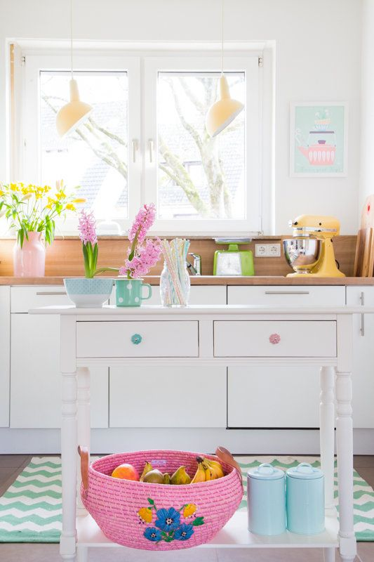a bright and fun kitchen with bright spring blooms, a pink basket with fruits and yellow pendant lamps over the space