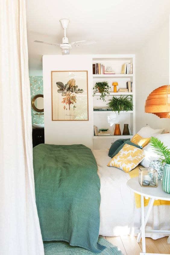 a fresh spring like bedroom with green and yellow bedding, with a botanical poster and some potted greenery
