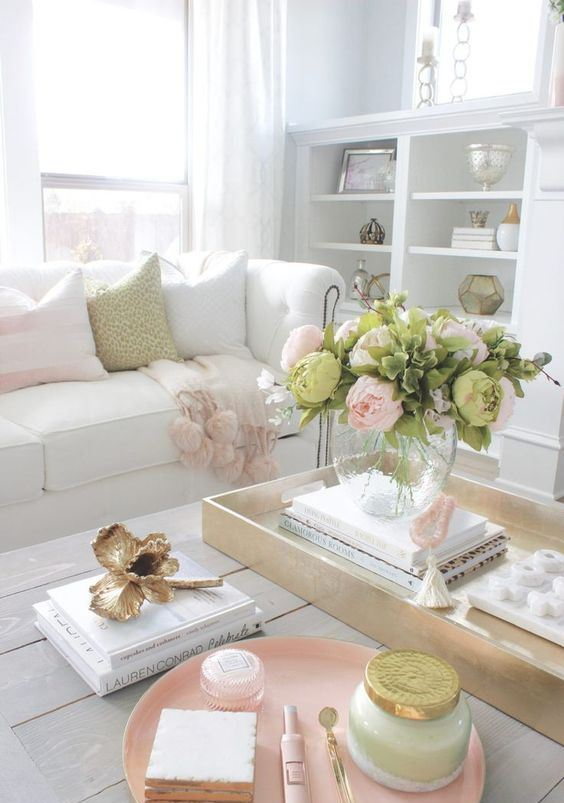 a soft and welcoming spring living room in neutrals and pink, with comfy and chic furniture, blooms and foliage plus pink accessories