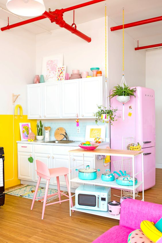 a colorful kitchen with a pink fridge, a yellow accent wall, bright turquoise tableware and a pink chair plus red pipes
