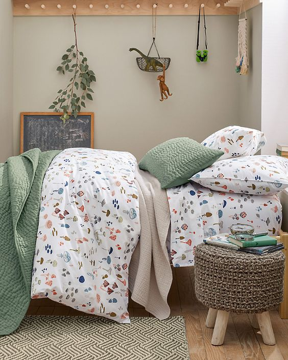 a fun and pretty bedding set with green and mushroom print pieces will give a slight woodland touch to the space