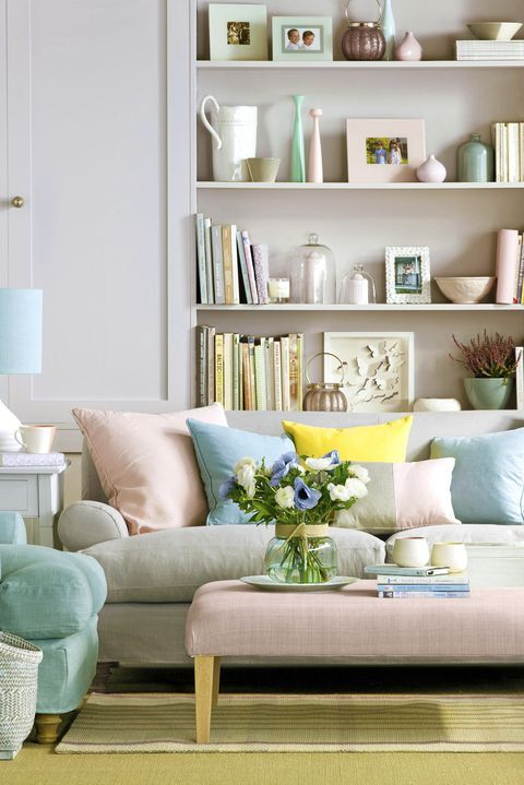 a soft pastel living room with blush walls, comfortable furniture in pastel shades and pastel pillows, pretty accessories in the same pastel shades