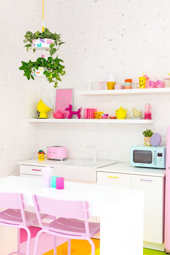a colorful kitchen with hot pink and yellow touches, pastel pink chairs, pastel handles, potted greenery gives much fun to the space