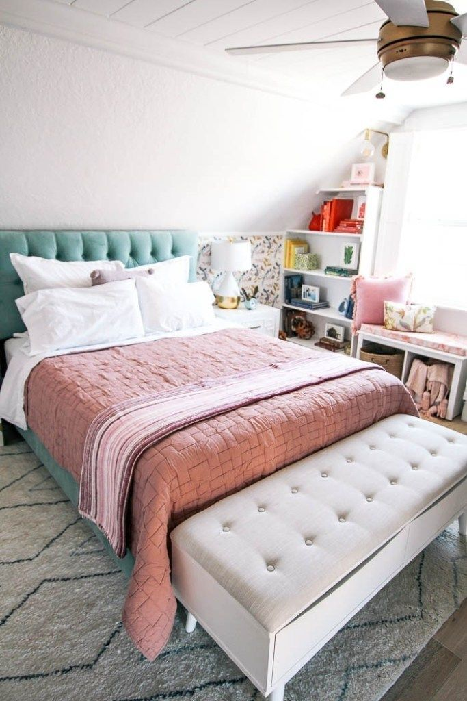 a lovely spring bedroom with a floral wallpaper wall, a green bed and some pink textiles for a spring feel