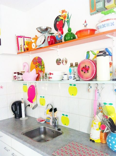 a colorful kitchen with open shelves, apple tiles, bright towels and tableware looks spring or summer ready at once