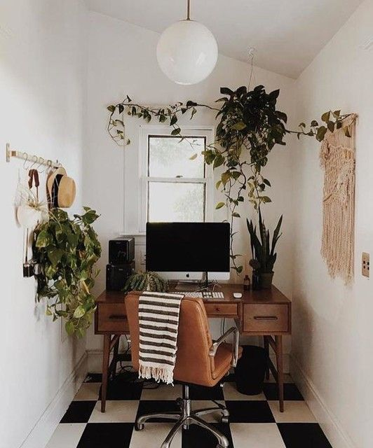 20 a small boho home office with a wooden desk, a leather chair, potted greenery and a macrame hanging is very cozy