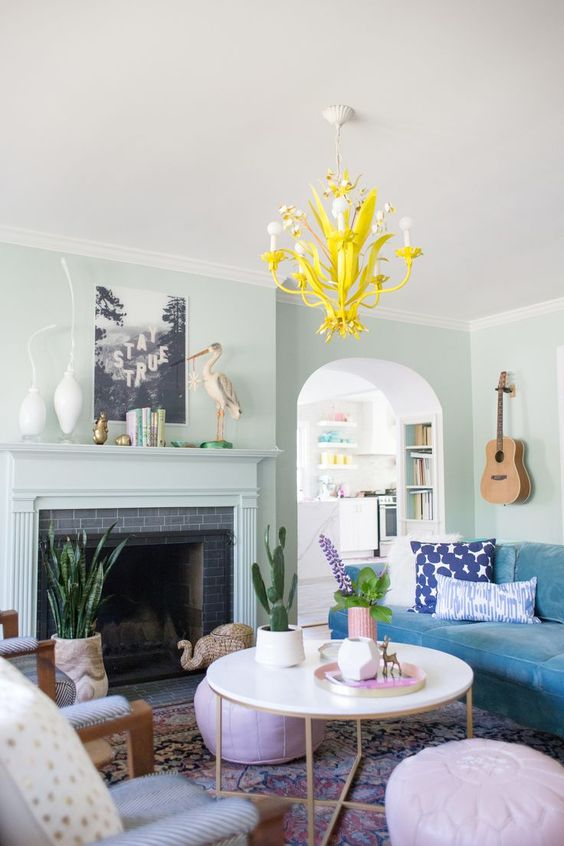 21 a pastel living room with light green walls, pretty pastel furniture and a bold blue sofa, a bright yellow chandelier and potted plants