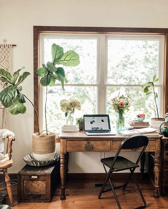 a vintage boho home office with a macrame hanging, dark stained wooden furniture, potted plants and cut blooms is welcoming