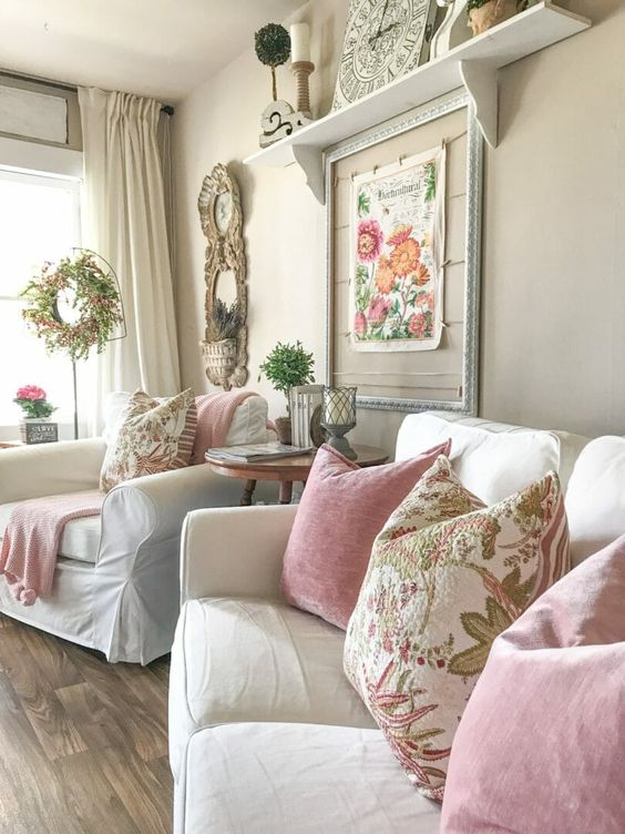 a vintage and shabby chic living room accented with floral prints - pillows, artworks and even a faux floral decoration