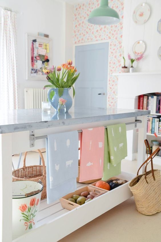 floral wallpaper, pastel towels and pink boxes with veggies, tulips in a vase give the kitchen a spring feel