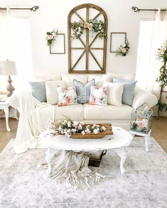 a welcoming shabby chic spring living room in neutrals, with floral pillows and faux blooms and greenery