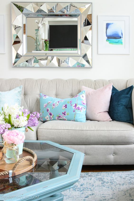a catchy spring living room with chic furniture, floral pillows and pastel ones, a blue hexagon table and a catchy mirror