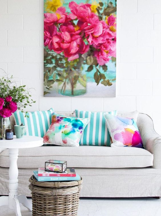a neutral living room with chic and elegant furniture, bright watercolor and floral printed accessories and a bold artwork