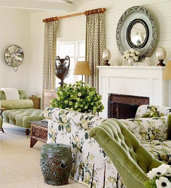 a vintage spring living room with green and floral print furniture, a fireplace, a porcelain green table and printed curtains