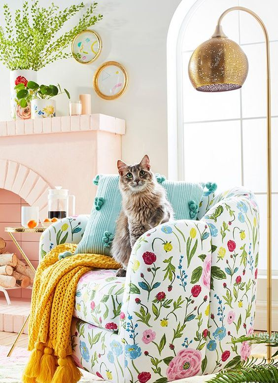 a bright and fun spring living room with a blush fireplace and a bold floral chair plus colorful accessories is very cool