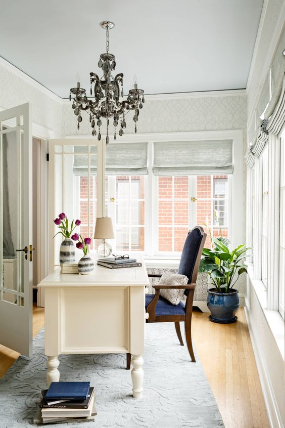 a pretty eclectic home office with bold tulips and potted greenery that bring a cool spring feel to the space