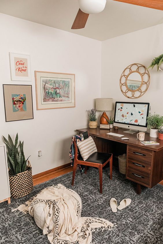 a mid-century home office with a rich stained desk, a leather chair, potted plants and a bright gallery wall feels very spring-like