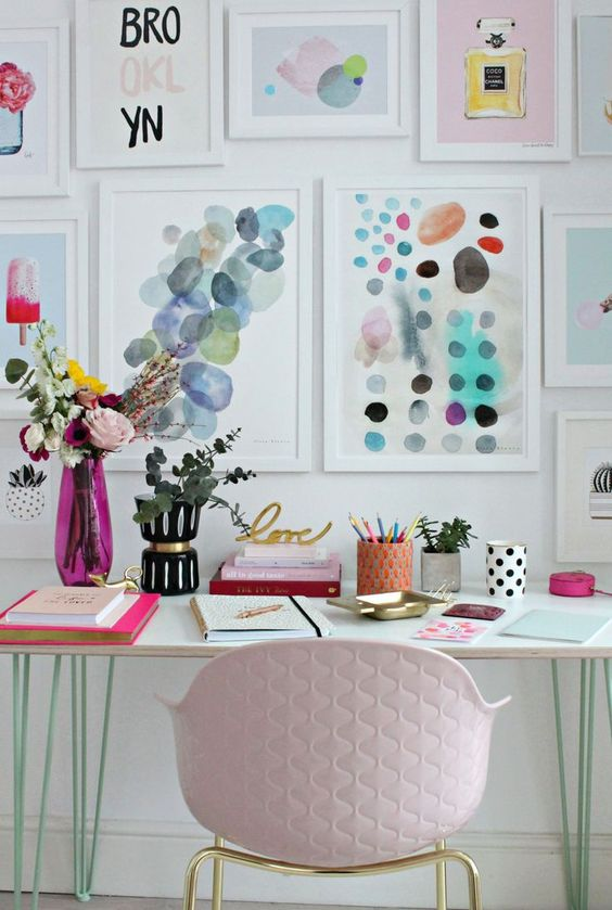 a charming home office with a gallery wall with colorful artworks, greenery and blooms and bright pink touches