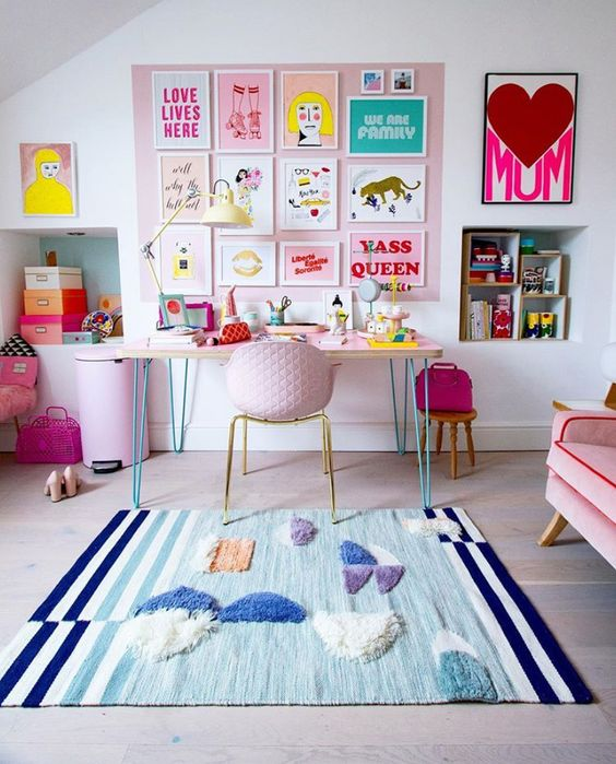 a colorful home office with a pink gallery wall and a sofa, a colorful artwork, a pink chair and a lilac trash bin