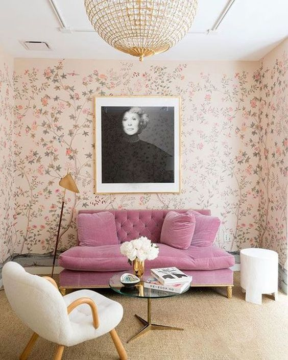a refined glam living room with blush floral wallpaper, a pink velvet sofa, a creative chair and a crystal chandelier