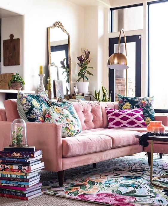 a bright living room with a pink sofa, floral pillows and a rug, potted plants, a mirror in a refined frame and a gold floor lamp