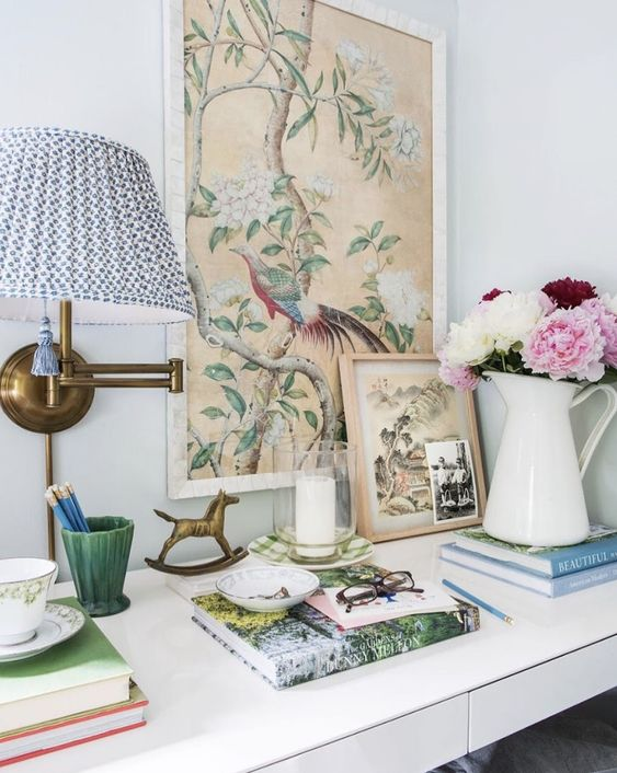 a home office space accented with vintage botanical artworks and cut blooms in a jug is a spring-ready space