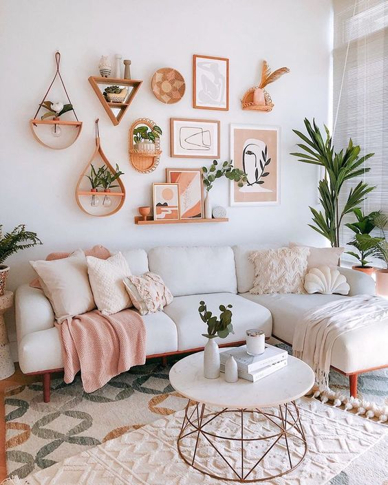 a pastel living room with chic neutral furniture, a gallery wall with various potted plants and greenery in vases
