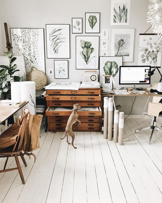 a light-filled Scandinavian home office with desks, chairs, a storage unit, a gallery wall with botanical prints