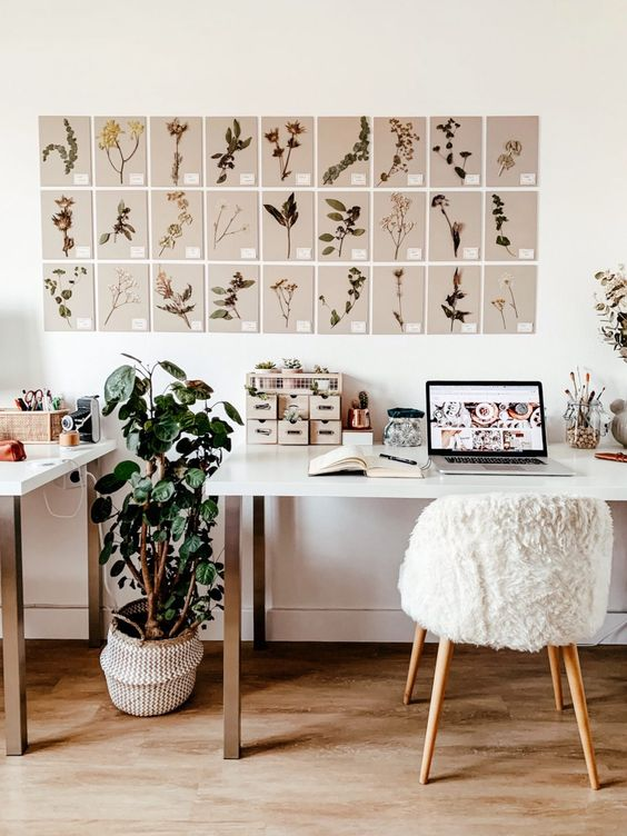 a neutral home office with a gallery wall with botanical posters, potted greenery and a couple of desks