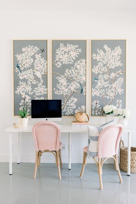 a spring home office with a shared desk, pink chairs, a trio of botanical posters and potted blooms
