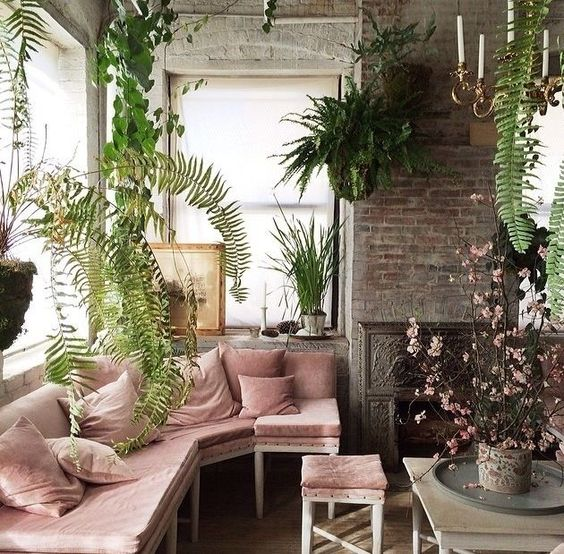 an industrial living room with brick walls, a fireplace, a pink curved seating and a stool plus potted greenery and blooming branches