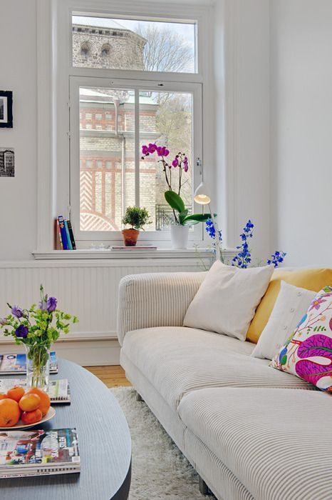 a neutral Scandinavian living room with a couple of bright touches, bold blooms in vases and pots