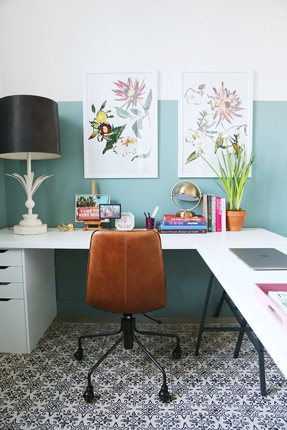 an airy home office with a blue color block wall, a trestle desk, leather chair, potted blooms and botanical posters