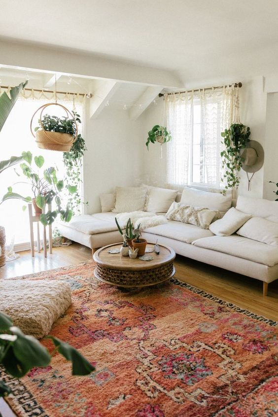 a boho living room with a bright rug, potted greenery and vines, a wooden table feels like spring