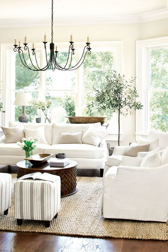 a neutral farmhouse living room with potted greenery and blooms, a vintage chandelier and striped ottomans