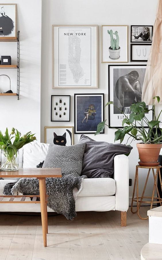 44 a Scandinavian living room in neutrals, a graphic gallery wall, greenery in vases and pots for a fresh touch