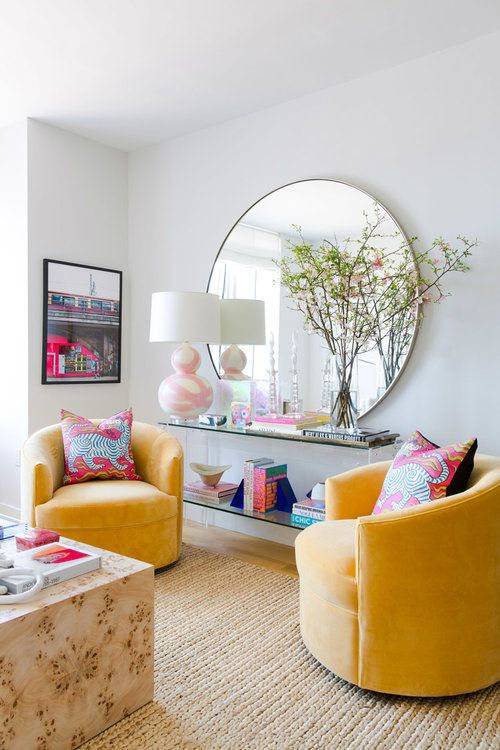 a bright living room with colorful furniture, printed pillows, blooming branches in a vase for a spring touch