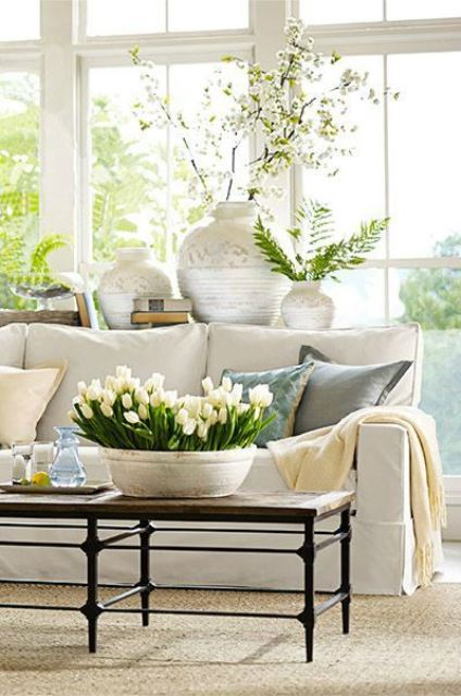 a spring living room in neutrals, with greenery and neutral blooms and pastel pillows for a fresh touch