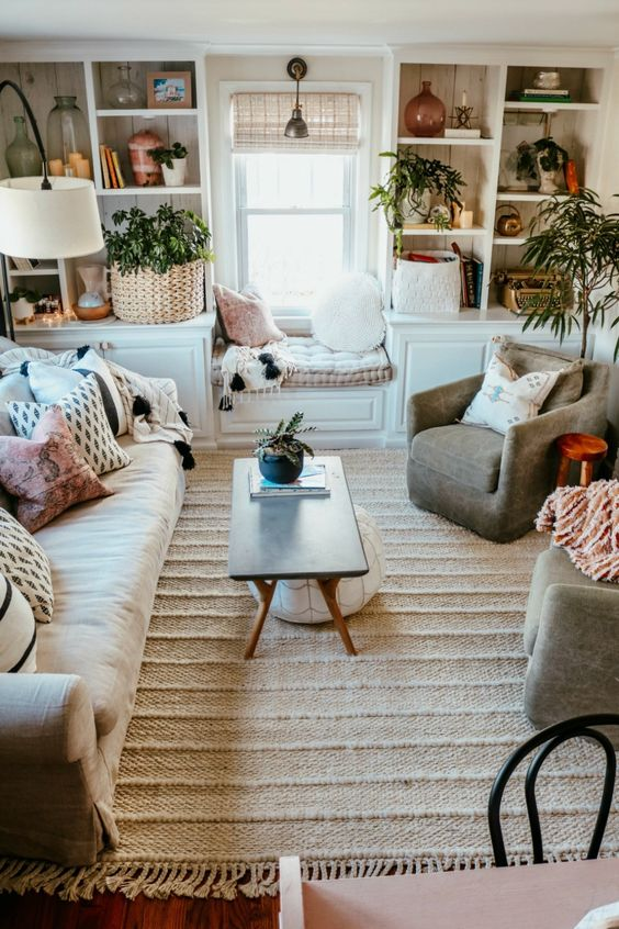 a small boho living room done in neutrals, with potted greenery that brings a fresh touch to the space