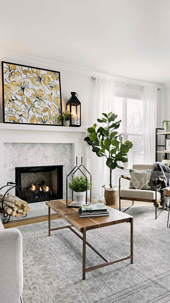 a modern neutral farmhouse living room with a potted tree and greenery, a floral artwork that give a spring feel to the space