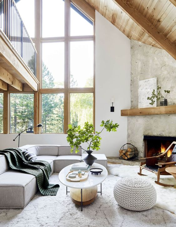a calm and peaceful neutral living room with a fireplace, grey furniture, greenery and a firewood stand