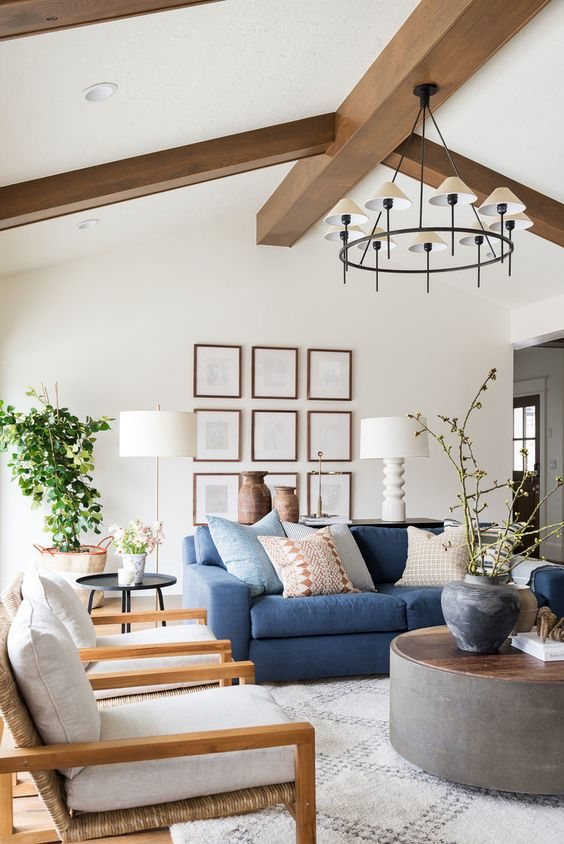 a stylish farmhouse living room with a blue sofa, neutral furniture, wooden beams, potted greenery and blooms