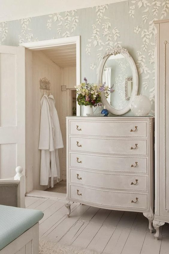 a French chic bedroom with light blue botanical wallpaper, neutral vintage furniture and a refined mirror and potted blooms