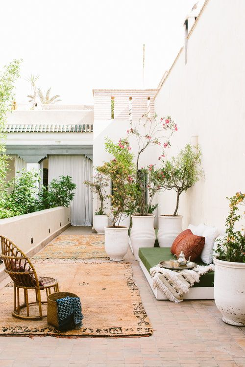 a Moroccan spring terrace in neutrals, with a rug, a daybed with pillows, a Moroccan blanket and a rattan chair