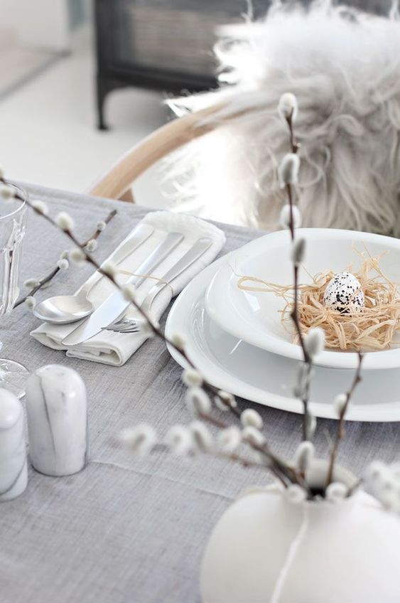 a Nordic Easter tablescape with a grey tablecloth, white porcelain, willow in a white vase, marble spice containers