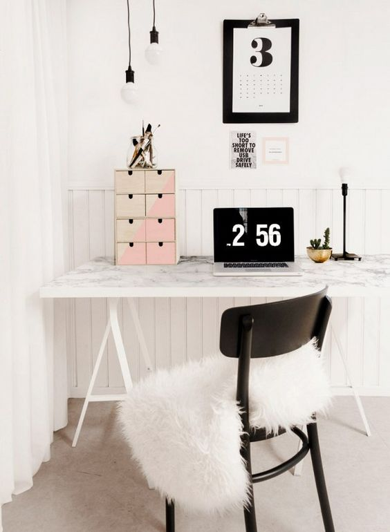 a Nordic work space with a trestle desk with a marble tabletop, a black chair, artworks and pendant bulbs