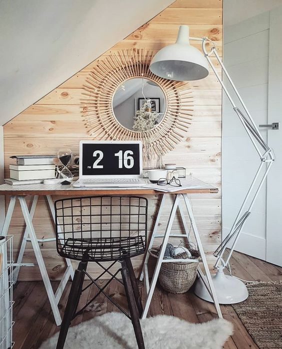 a Nordic working nook with a white trestle desk, a black metal chair, a white floor lamp and a sunburst mirror