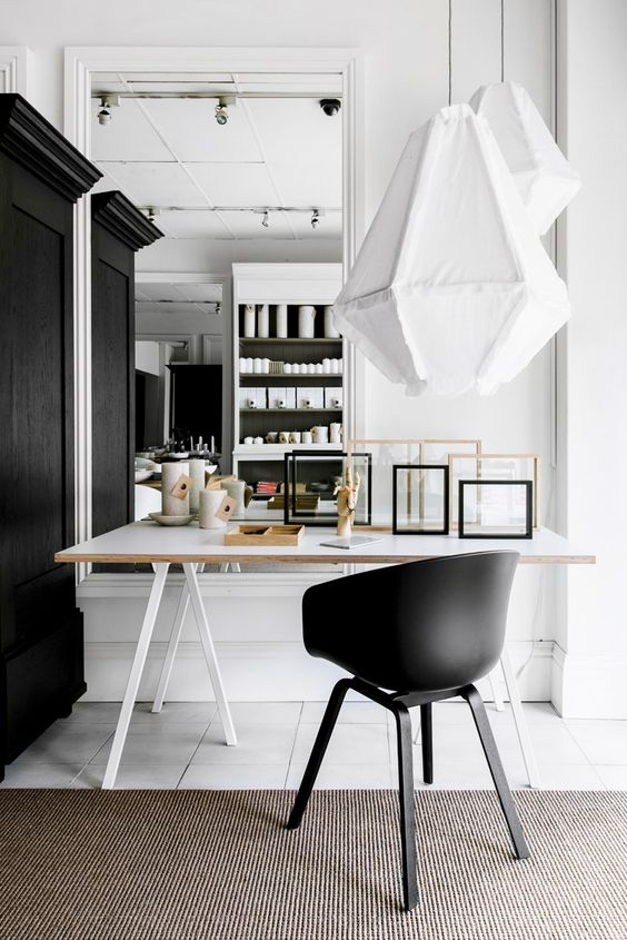 a Nordic working space with a white modern trestle desk, a black chair, empty frames and catchy pendant lamps
