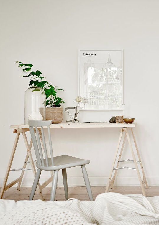 a Nordic workspace with an airy folding trestle desk, a grey chair, some greenery and art is a pretty space to be