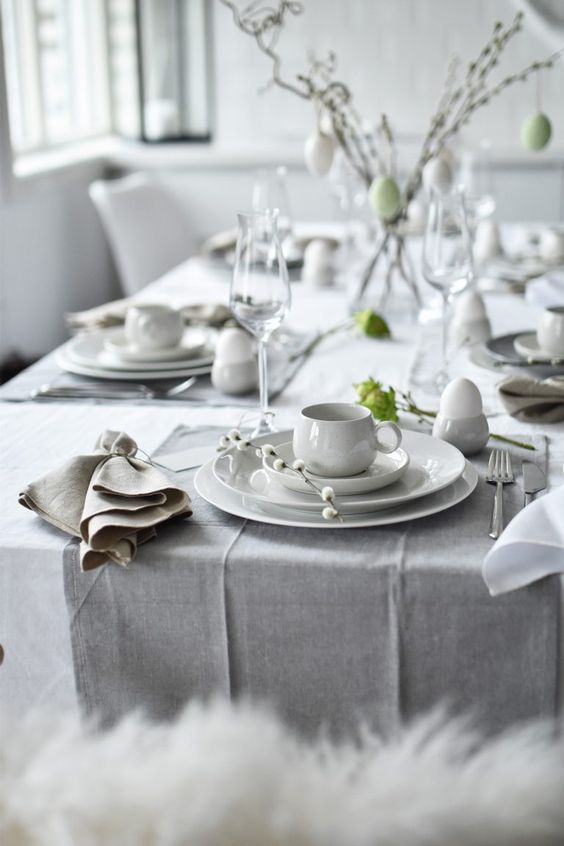 a Scandinavian Easter table setting with grey and white linens, chic porcelain, willow and greenery plus lots of eggs